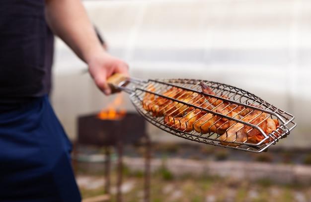 Mann, der fleisch auf dem grill kocht. sommerspaß. Premium Fotos