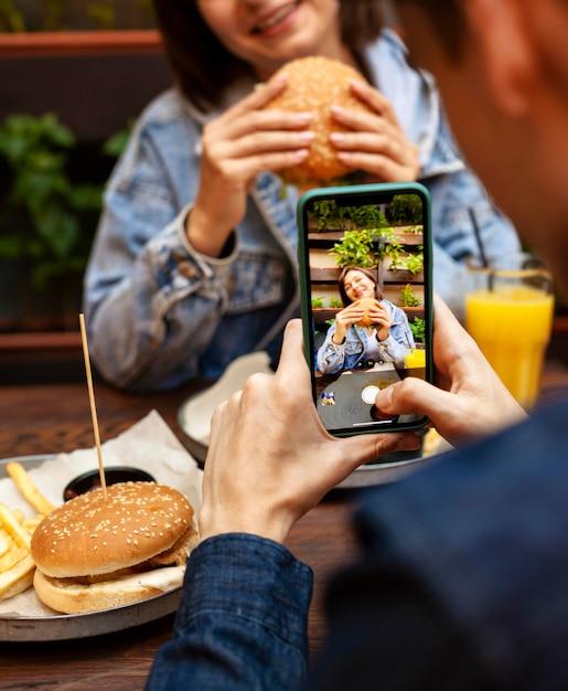 Mann, der foto der frau isst, die burger isst Premium Fotos