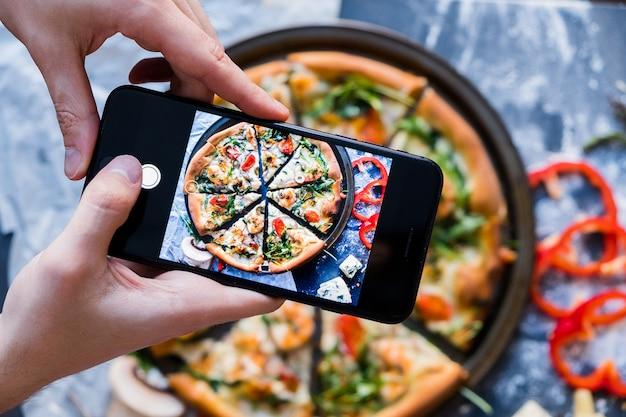 Mann, der foto der pizza mit smartphone nahaufnahmeansicht des prozesses Premium Fotos