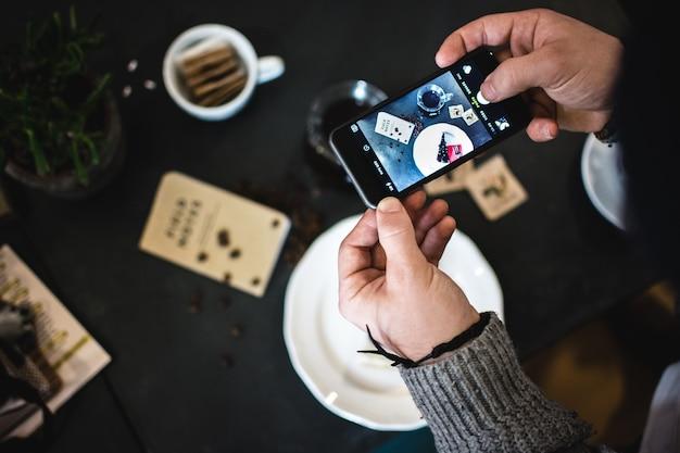 Mann, der foto des kaffees und des kuchens mit seinem telefon macht Kostenlose Fotos