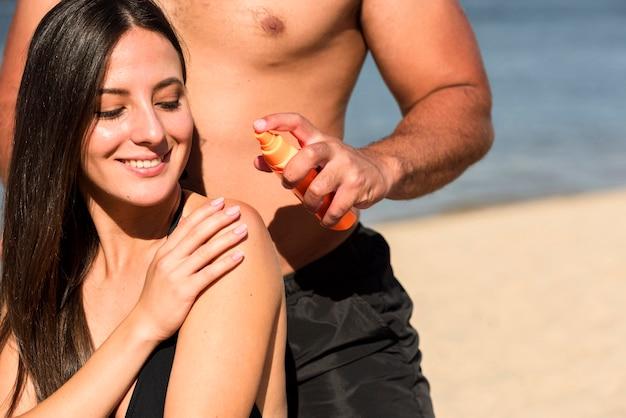 Mann, der frau hilft, sonnenschutz am strand anzuwenden Kostenlose Fotos