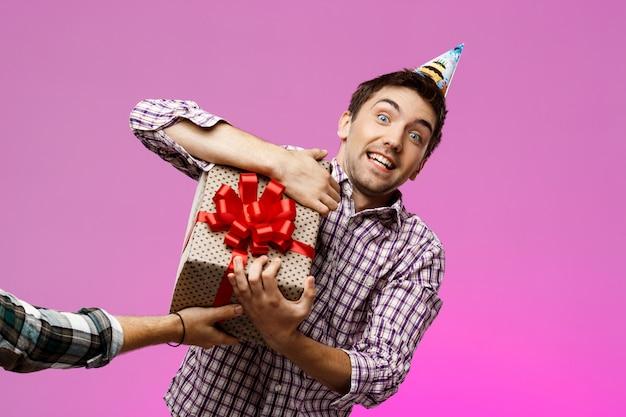Mann, der geburtstagsgeschenk im kasten über lila wand herausreißt. Kostenlose Fotos