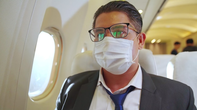 Mann, der gesichtsmaske in einem flugzeug trägt Premium Fotos
