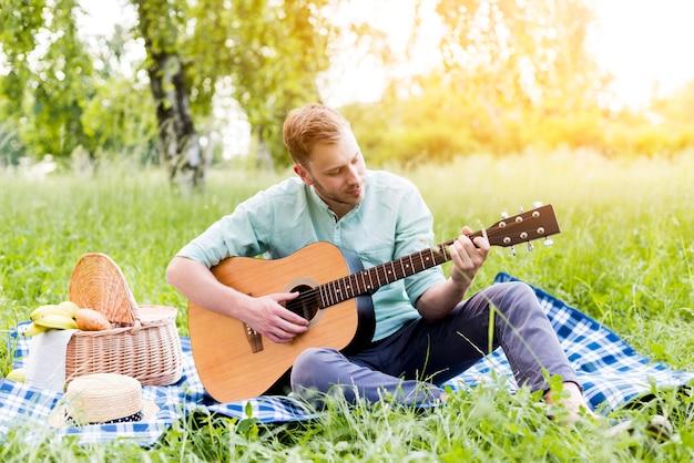 Mann, der gitarre auf picknick am sommer spielt Kostenlose Fotos