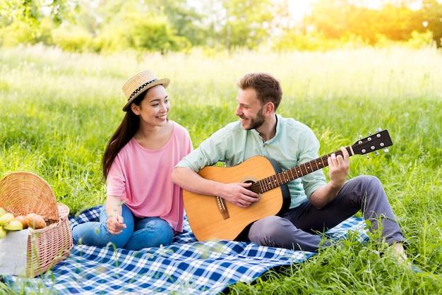 Mann, der gitarre für frau spielt Kostenlose Fotos