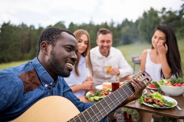 Mann, der gitarre für seine freunde an einem grill spielt Premium Fotos