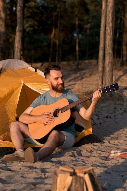 Mann, der gitarre nahe bei zelt spielt Kostenlose Fotos