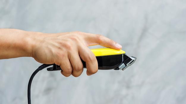 Mann, der haarscherer in seiner hand hält. Premium Fotos