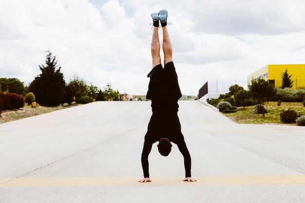 Mann, der handstandübung auf straße tut Kostenlose Fotos