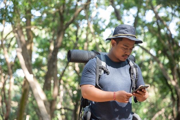 Mann, der handy im wald benutzt | Premium-Foto