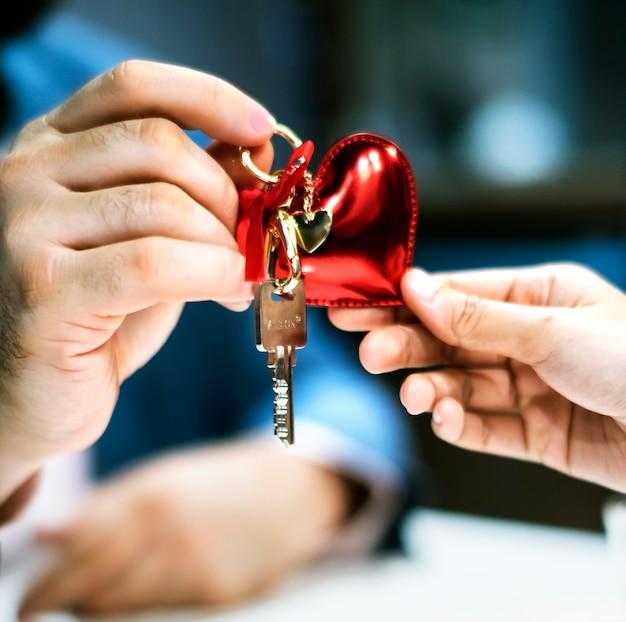Mann, der hausschlüssel als geschenk führt Kostenlose Fotos