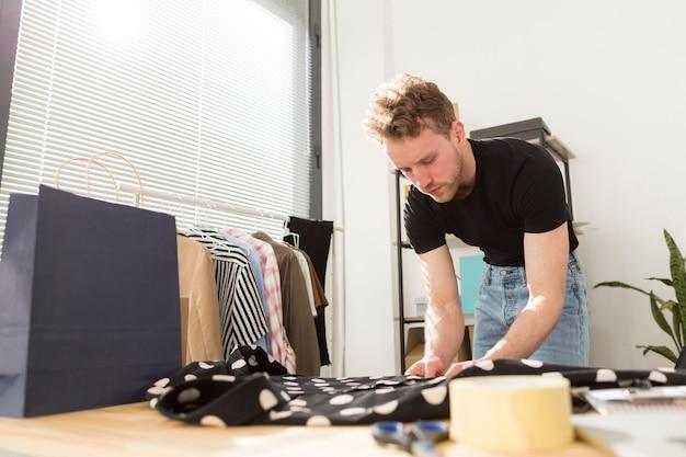 Mann, der hemd mit punkten faltet Kostenlose Fotos