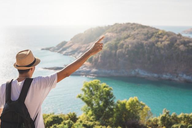 Mann, der hut trägt, hält seine hand glücklich. mann asiatischer tourist betrachten sie berge und das meer vor sonnenuntergang. für aktivität lebensstil im freien freiheit oder reisetourismus inspiration backpacker tourist zu covid 19 Premium Fotos