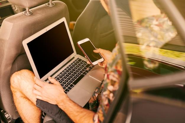 Mann, der im auto mit laptop und smartphone sitzt Kostenlose Fotos