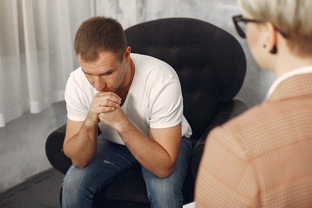 Mann, der im büro des psychologen sitzt und über probleme spricht Kostenlose Fotos