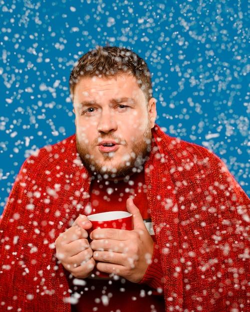 Mann, der im schnee beim halten einer schale bleibt Kostenlose Fotos