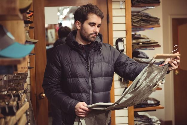 Mann, der in einem bekleidungsgeschäft einkauft Kostenlose Fotos