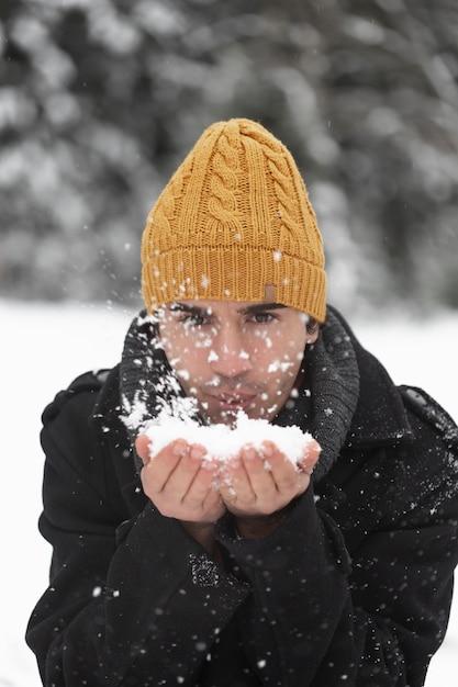 Mann, der in einem haufen schneeansicht bläst Kostenlose Fotos