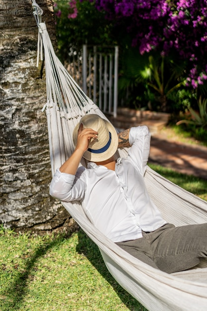 Mann, der in einer hängematte im garten sich entspannt. Kostenlose Fotos