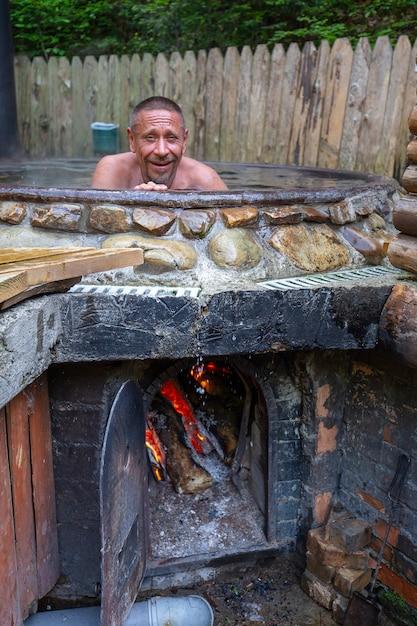 Mann, der in gusseisernem bottich mit schwefelwasserstoff enthaltendem mineralwasser badet Premium Fotos