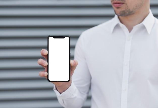 Mann, der iphone modell hält Premium Fotos