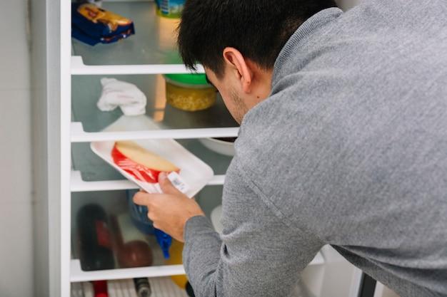 Mann, der käse vom kühlschrank nimmt Kostenlose Fotos