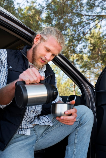 Mann, der kaffee trinkt und neben auto sitzt Kostenlose Fotos