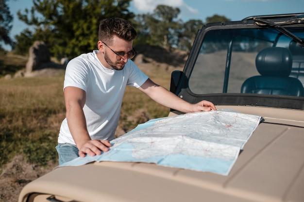 Mann, der karte während der fahrt mit dem auto überprüft Kostenlose Fotos