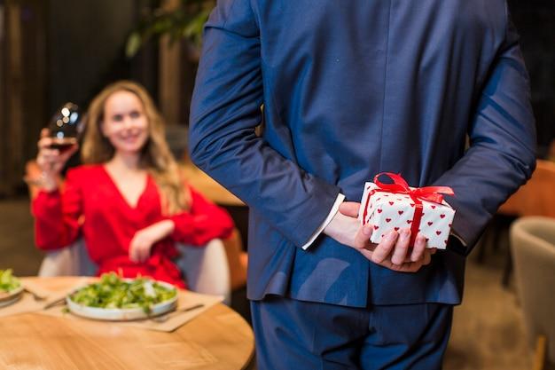 Mann, der kleine geschenkbox hinten zurück hält Kostenlose Fotos