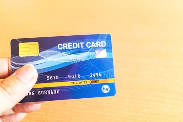 Mann, der kreditkarte auf laptop hält. online-shopping im internet mit einem laptop Premium Fotos