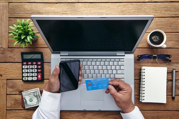 Mann, der kreditkarte hält und laptop-computer verwendet. Premium Fotos