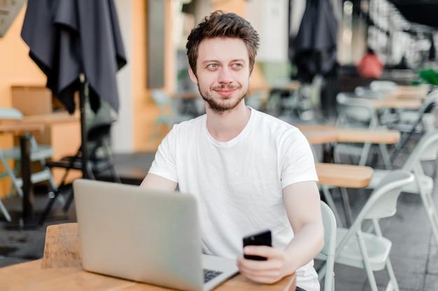 Mann, der laptop für fernarbeit im café verwendet Premium Fotos