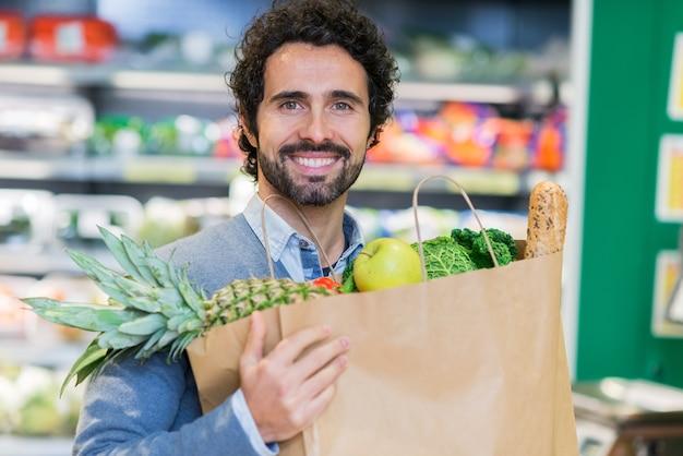 Mann, der lebensmittelbeutel in einem gemischtwarenladen hält Premium Fotos