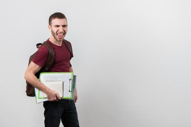 Mann, der lustige gesichter mit exemplarplatzhintergrund bildet Kostenlose Fotos