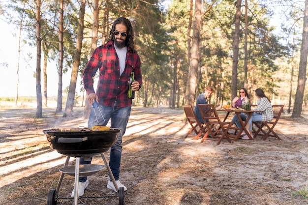 Mann, der mais auf dem grill röstet, während freunde sich am tisch unterhalten Kostenlose Fotos