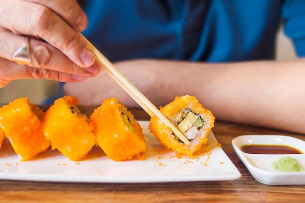 Mann, der maki sushi isst Kostenlose Fotos