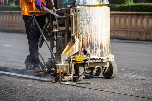 Mann, der maschine verwendet, um verkehrslinie streifen auf der straße zu machen Premium Fotos