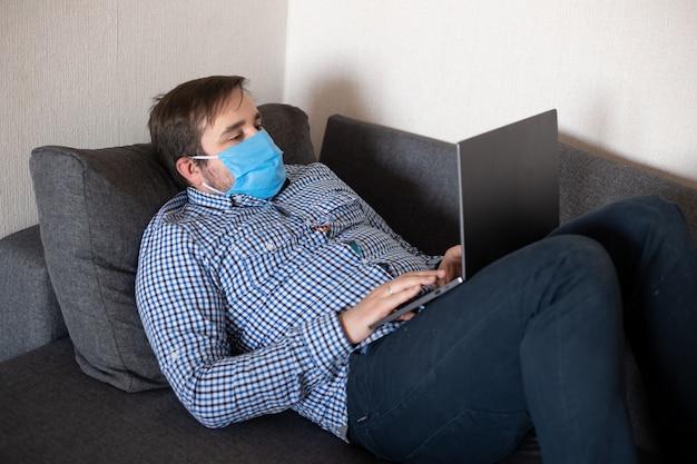 Mann, der maske arbeitet, die mit computer vom hauptbüro arbeitet, das auf sofa, coronavirus, krankheit, infektion, quarantäne, medizinische maske liegt Premium Fotos