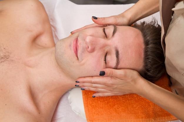 Mann, der massage in der schönheitsmitte erhält Premium Fotos