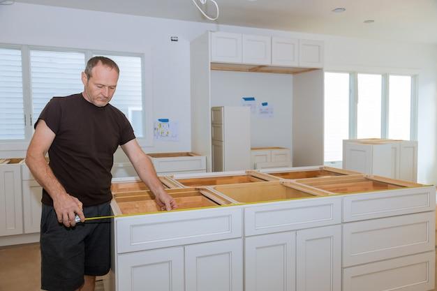 Mann, der maßband für das messen der größe in der modernen küche für heimwerker verwendet. Premium Fotos