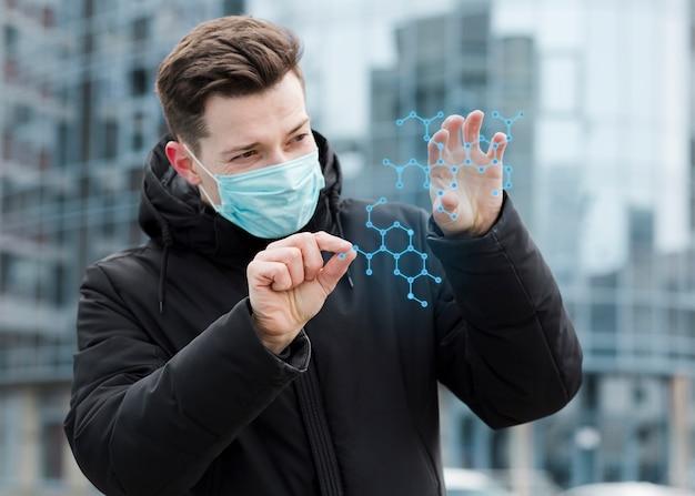 Mann, der medizinische maske trägt und molekulare struktur betrachtet Kostenlose Fotos
