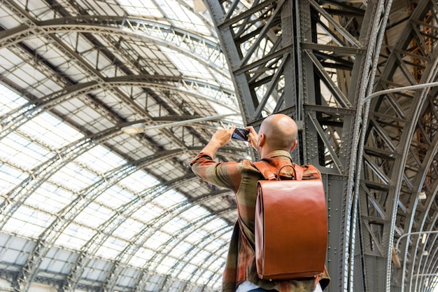 Mann, der mit dem rucksack macht fotos reist Kostenlose Fotos