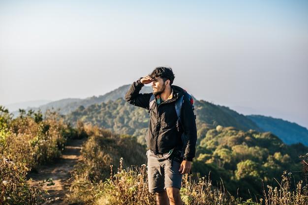 Mann, der mit dem rucksack wandert in berge reist Kostenlose Fotos