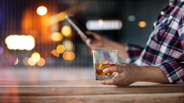 Mann, der mit einem bourbon-whisky-getränk entspannt Premium Fotos