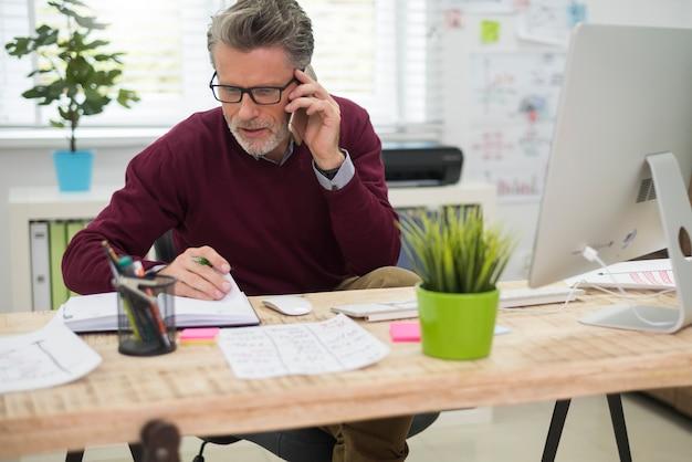 Mann, der mit einem seiner kunden am telefon spricht Kostenlose Fotos