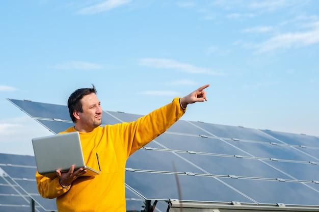 Mann, der mit sonnenkollektoren arbeitet Premium Fotos
