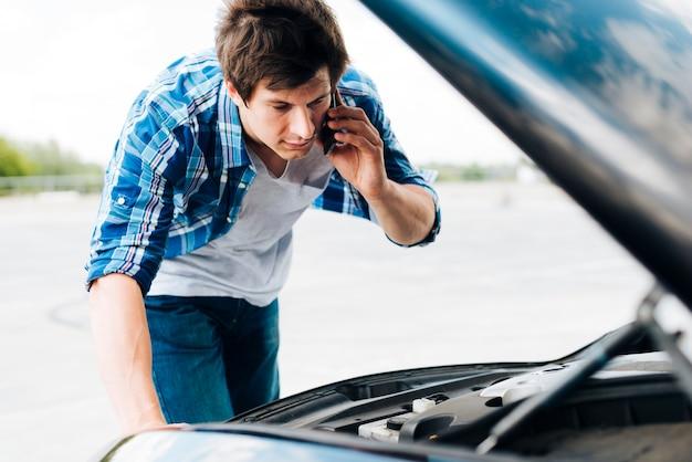 Mann, der motor überprüft und am telefon spricht Kostenlose Fotos