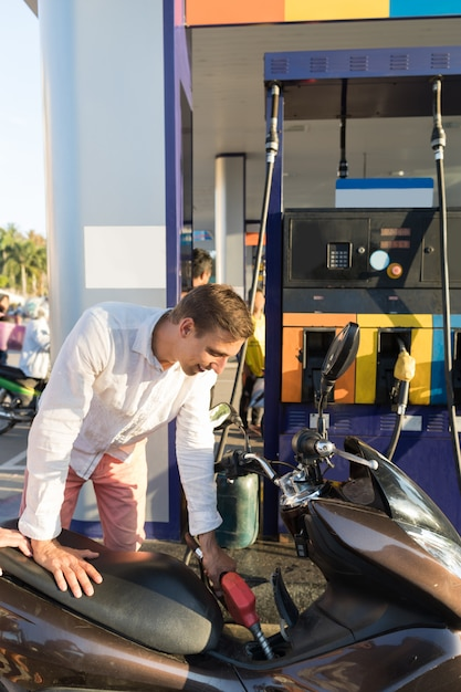 Mann, der motorrad auf stations-motorradfahrer-benzin-fahrrad tankt Premium Fotos