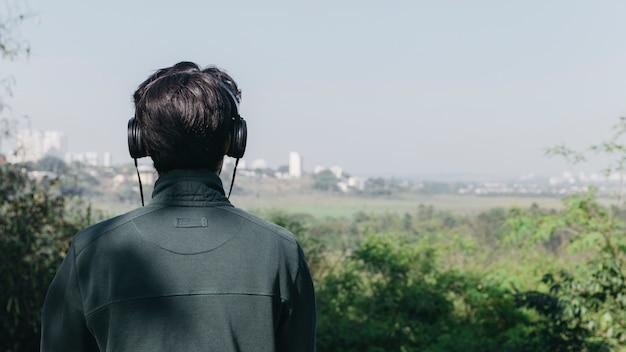 Mann, der musik in der natur hört Kostenlose Fotos