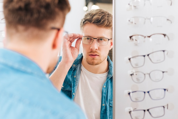 Mann, der nach neuen gläsern am optometriker sucht Kostenlose Fotos